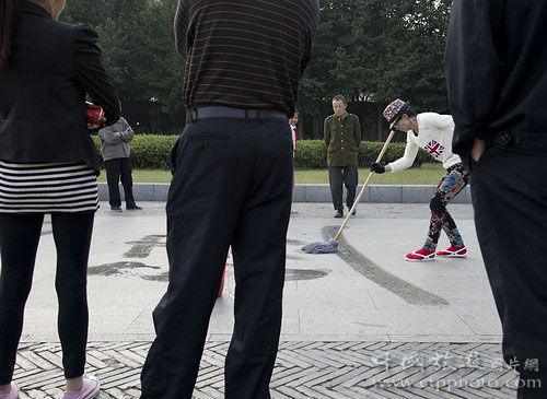 一名书法家在杭州公园用拖杷写字