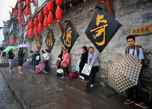 """4月29日17时23分,一对情侣在沱江边观赏景致。""""门票新政""""最重要的影响就是散客人数的大量减少。"""