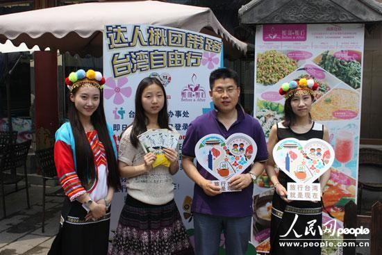 顾客与戴着台湾特色头饰的姑娘合影