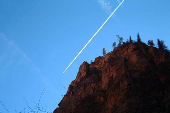 抬头仰望蓝天,飞机在天空中划出一道白线