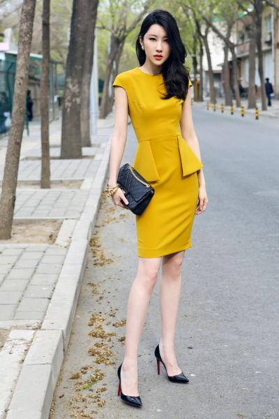气质美女着姜黄连衣裙手包黑高跟为造型点睛