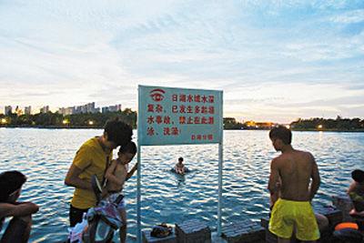 昨天傍晚,不少市民在日湖里游泳,旁边立着的警示牌完全被忽视。 记者 唐严 摄