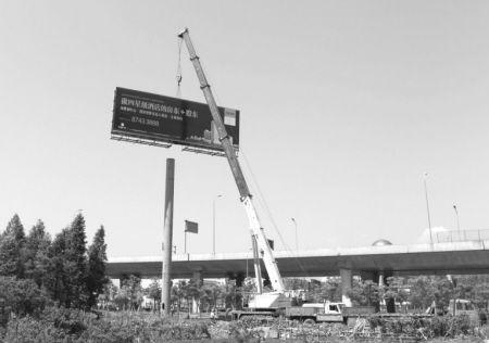 有关人员正在拆除广告牌。记者 刘波 摄