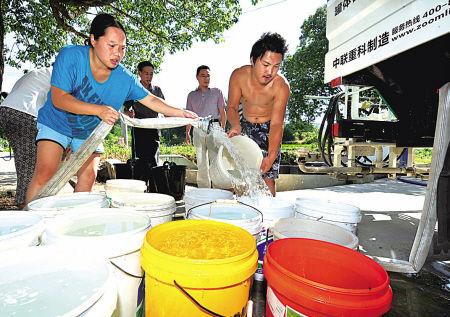 上月底起,该县环卫处每天派出一辆洒水车载着10吨清水进村救急。(严龙 陈云松 邵映菡 摄)