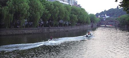 8月5日傍晚,几名冲浪爱好者或驾游艇或踏冲板在姚江上秀技消暑,引来路人注目。(吴大庆 摄)