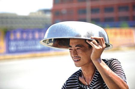 6日中午,在余姚市兰江街道直江路,一名行人头顶不锈钢脸盆抵挡烈日烤晒。(陈斌荣 摄)