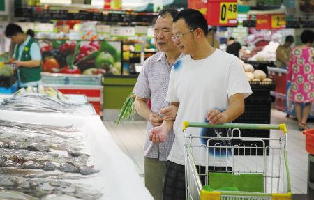 早上7点多,小蔡陪着盲人闻师傅在超市买菜。 (记者 许天长 摄)