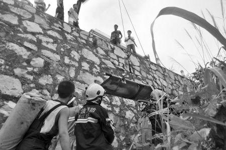 消防队员把运送伤员的担架吊到马路上
