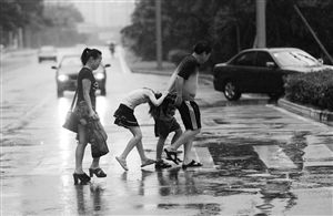 昨日下午,一阵滂沱大雨之后雨势渐缓,鄞州四明东路,小孩子钻到大人衣服下躲雨。