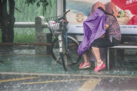 在惊驾路公交车候车亭,一对母女无法前行,在候车亭下躲雨。