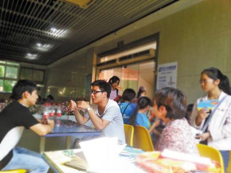 杨战胜(右边戴眼镜者)在和受助的学弟交谈。