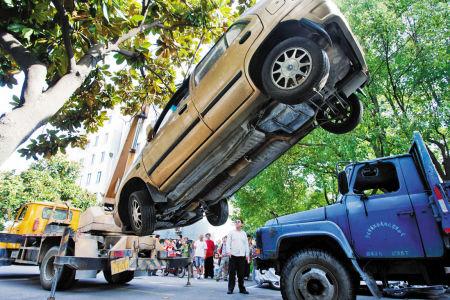 """昨天在联南社区,一辆""""无主""""车被吊车拖走。记者 唐严 摄"""