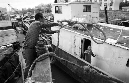 昨天,在甬江边停靠着十几艘避风的舟山籍货船。下午风势渐大,船员们用缆绳将几条船连在一起,以共同防范台风。记者 许天长