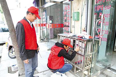 志愿者正在上门为塑料城的经营户维修家电。(张 燕 张松高 摄
