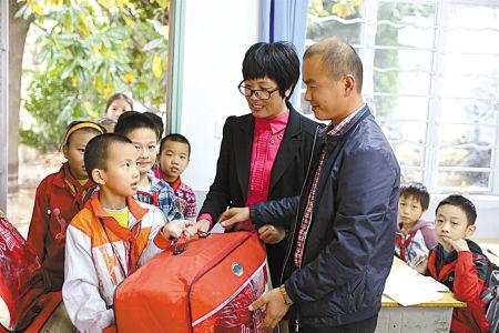 图为袁城丰向女儿班级的贫困孩子送上棉被。(吴大庆 摄)