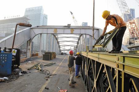 图为昨天,施工人员在灵桥大修现场起吊钢构和组装贝雷梁。