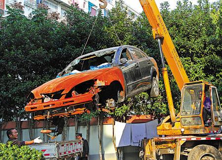 昨天,海曙花苑新村内一辆被爆竹烧毁的轿车被吊走。