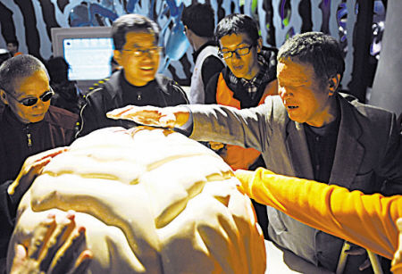 在宁波科学探索中心,盲人朋友在志愿者的指引下触摸科普展品。(记者 丁安 摄)
