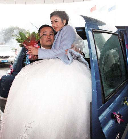 幸福的新郎抱着幸福的新娘走下出租车。 孙红军 摄