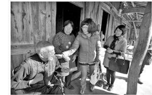 邓凯丽(左三)在大堰镇枫树林白竹岗自然村,给胡未聪送上400元红包。