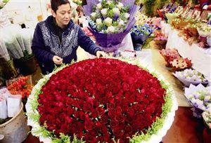 图为一家花店的主人在小心打理客人预订的999朵玫瑰组成的情人节花束