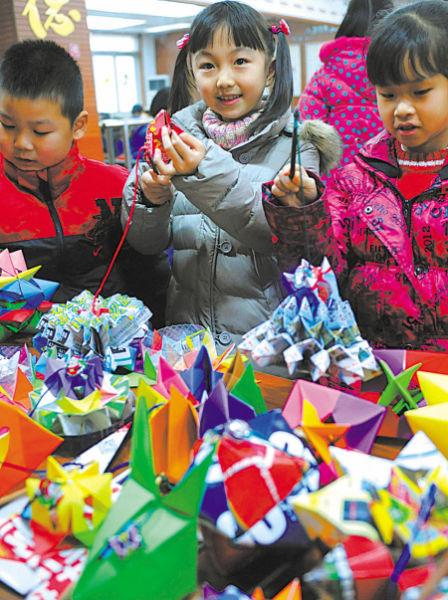 折纸艺人向儿童传授折纸技巧