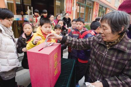 """昨天下午,在黄鹂小学,附近居民和同学们一起,参加""""最美宁波人""""评选投票活动。 记者 唐严 摄"""