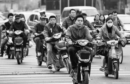 昨天,不少市民骑电动自行车经过灵桥路口。 记者 唐严 摄