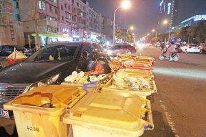 25日晚上7点左右,兴裕新村门口已经摆放了许多垃圾桶,一辆汽车被围住。 记者 王鹏 摄