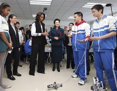 彭丽媛与米歇尔观看学生们演示自己设计制作的几何机器人