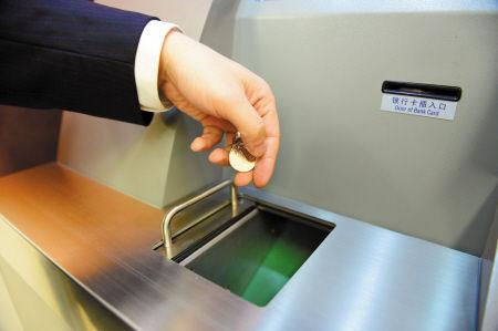 把硬币放进自助兑换机储币斗