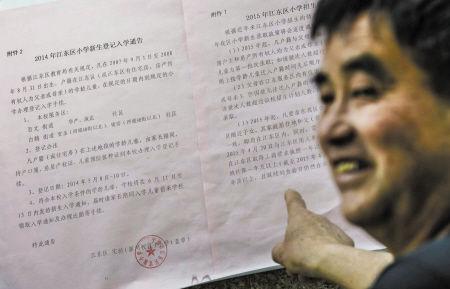 市民正在江东实验小学门口看招生告示。 记者 徐佳伟 摄