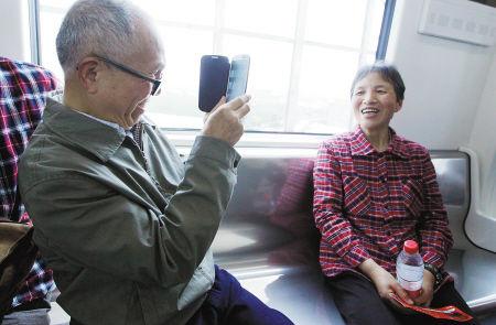 在车厢内,七旬老人朱秀良为妻子张凤书拍照留念。记者 许天长 摄