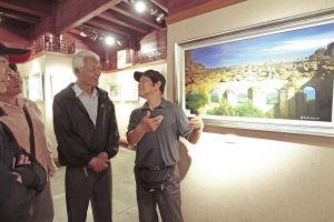 胡惠昌用手语介绍自己的作品。 记者 王鹏 摄