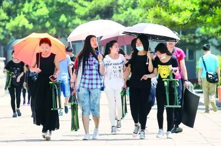 晴热天气市民打伞出行。