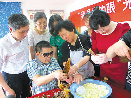 社区志愿者与盲人一起包粽子