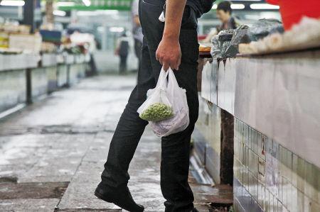 一市民在菜市场提着用违规塑料袋装的菜。 记者 许天长 摄