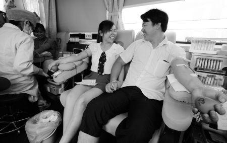 罗卫芳第一次参加献血有点紧张,一起献血的丈夫蒋伟握着她的手安慰她。记者 许天长