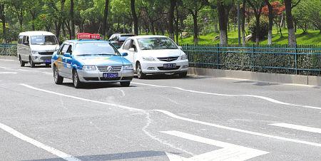 高低不平的路面,把车道分隔线扭成了曲线,令司机发怵。 (记者 余建文 摄)