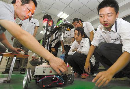 图为许多学生对机器人课程兴趣十足。