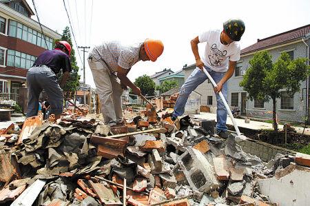 昨日上午,余姚郎霞街道镇西村村民正在主动拆除辉桥江边最后几处违法建筑。(胡建华 摄)