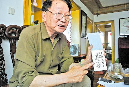 """胡佩庸在展示父亲留下的7字""""家训""""。(冯小平 摄)"""