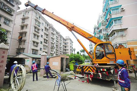 """电力人员在柳馨花园小区进行""""三双""""施工。(冯瑄 王幕宾 摄)"""