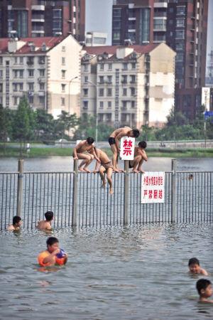 水域现场有醒目的警示标语,仍不时有人翻越围栏游泳,其中还有不少儿童。记者 崔引 摄