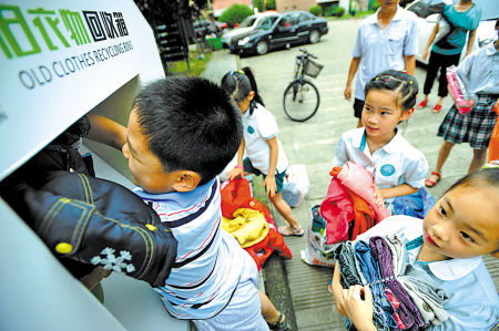青少年将旧衣投入旧衣物回收箱