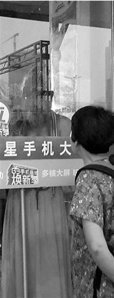 隔着玻璃,王冬藕阿姨仔细看着犀利爷爷。 邹洪珊 摄