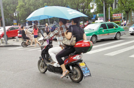 加装遮阳篷后还骑车带人。 记者唐严昨天下午摄于药行街