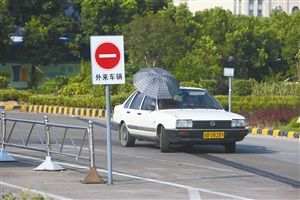 宁波一所驾校内,大太阳下,学员打着伞学车