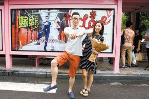 吴先生在印有他和女友婚纱照的公交站广告牌前向女友求婚。记者徐文杰实习生陈哲摄