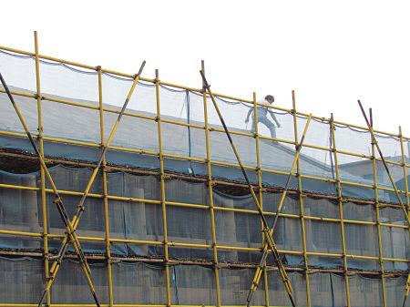 在鄞奉路汽车南站至长丰桥段的一处建筑工地,有人未戴安全帽在坡状屋顶上行走。 (杨静雅 摄)